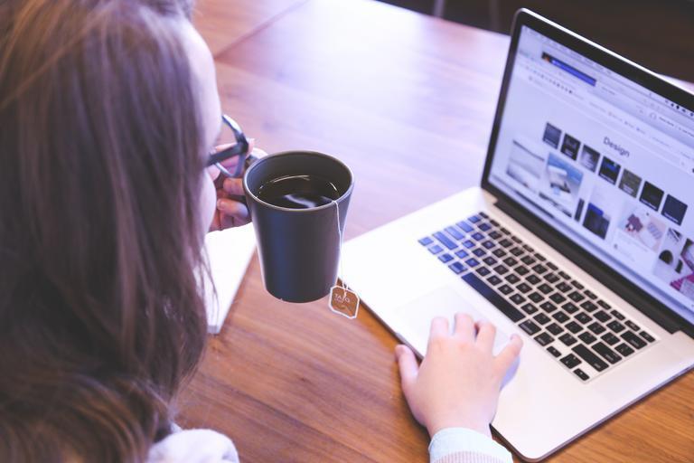 žena pije kávu a hledá info na internetu